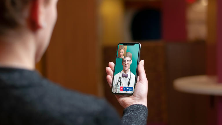 Close up of mobile phone in hand doing video call with doctor