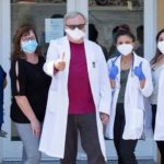 Group of medical providers in lab coats and wearing masks giving thumbs up