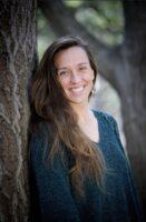 Medical provider headshot of female with long brunette hair resting against tree