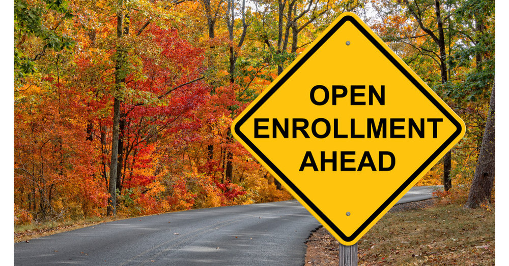 Open enrollment yellow traffic sign with fall foliage and street behind the sign